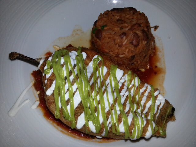 Chili relleno (stuffed chili pepper) with rice and beans on the side