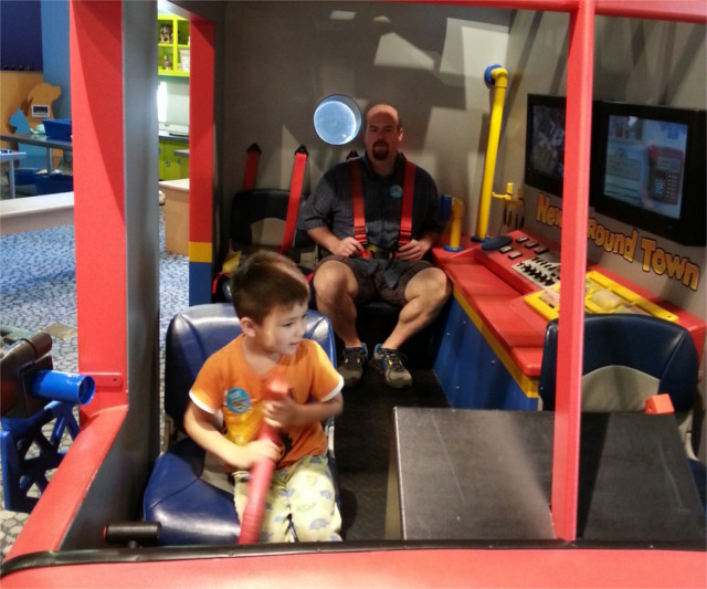 Free visit to the children's museum. I'm strapped in with the little dude at the flight stick. HELP!!